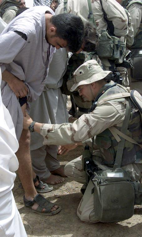 NAV2003041608-CENTRAL COMMAND AREA OF RESPONSIBILITY, Iraq,  April 8 (UPI)-- Hospital Corpsman 2nd Class Charles Taylor examines an Iraqi man during a humanitarian visit to an Iraqi village.  Clean water and medical care were part of the humanitarian aid provided in support of Operation Iraqi Freedom.  Operation Iraqi Freedom is the multi-national coalition effort to liberate the Iraqi people, eliminate Iraqi's weapons of mass destruction, and end the regime of Saddam Hussein.  jg/pcj/Lance Cpl. Alicia M. Anderson   UPI