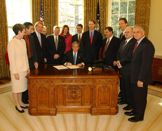 President George W. Bush pauses before signing the Controlling the Non-Solicited Pornography  and Marketing Act of  2003, which establishes a framework of administrative, civil and criminal tools to help America?s consumers, businesses and families combat SPAM. Pictured with the President are from left to right: Rep. Heather Wilson, (R, NM); Garry Betty, President and CEO of Earthlink; Rep. Edward Markey (D, MA); Rep. Rick Boucher (D, VA); Sen. Conrad Burns (R, MT); Rep. Melissa Hart (R, PA; Sen. Bill Frist (R, TN); Sen. Ron Wyden (D, OR); Rep. Chris Cannon (R, UT); Jonathan Miller, Chairman and CEO of America Online; Maynard Webb, Chief Operating Officer of eBay; Rep. Gene Green (D, TX).   (UPI Photo/Tina Hager/White House)