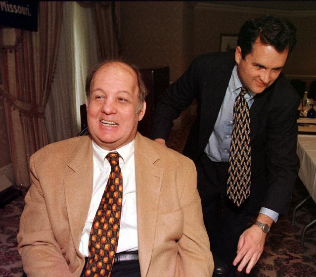 SLP99031205- 12 MARCH 1999- CLAYTON, MISSOURI, USA:  James Brady, the former White House press secretary wounded in an assination attempt on President Ronald Reagan in 1981, gets help with his wheelchair by Joe Sudbay, after speaking to reporters about the need for handgun control as Missouri gets ready to vote on Proposition B, the law that would permit Missourians to carry concealed weapons, March 12. bg/ rw/Bill Greenblatt      UPI