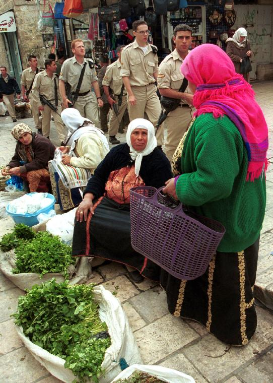 JER2000072406 - 24 JULY 2000 - JERUSALEM, ISRAEL: Israeli soldiers walk past Palestinian women selling goods in the Moslem Quarter of the Old City of Jerusalem, July 24, as Israeli Prime Minister Ehud Barak and Palestinian leader Yasser Arafat meet with US President Bill Clinton on the 14th. day of the Camp David Summit in Maryland.  The negotiators are reported to be meeting around the clock in an effort to reach an agreement on the future of Jerusalem and other final status issues which would end the 52 year old Israeli/Palestinian conflict.  jr/dh/Debbie Hill UPI