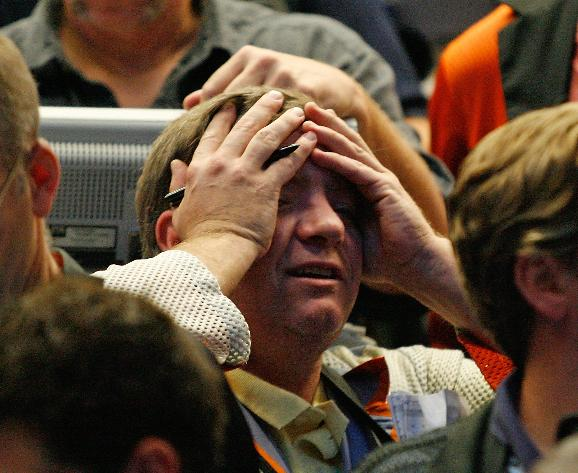 Stocks collapse in the wake of the government bailout of AIG: A trader covers his face in the S&P 500 options pit at the Chicago Board Options Exchange on September 17, 2008 in Chicago. The S&P 500 closed down 57 points at 1,156.39 and the Dow lost nearly 450 points closing at 10,609.66 amid investor anxieties about the financial system following the government's bailout of insurer American International Group, Inc. on Tuesday. (UPI Photo/Brian Kersey)