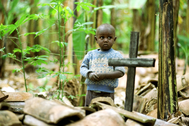 WAX2003091001 - WASHINGTON, Sept. 11 (UPI) -- A young Ugandan boy stands by the grave of his parent who died of HIV/AIDS in 1997.  The boy is being raised by a 93-year-old grandmother.   To go with story AIDS-AFRICA.   aat/Bill Youngblood/World Vision Photo  UPI