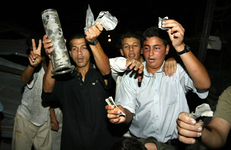 ISRAELI AIRCRAFT LAUNCH A SECOND SERIES OF AIRSTRIKES IN GAZA-Palestinian civilians  carry pieces from missiles in Khan Younis in Gaza Strip after Israeli helicopters fired missiles at Palestinian targets on July 16, 2005 in the Gaza Strip. Israeli aircraft launched a second series of airstrikes in Gaza City and the southern Gaza town of Khan Younis early Saturday. Two people were injured in the attacks. On Friday, Israeli air strikes killed five in the West Bank and Gaza, four of them Hamas militants.   (UPI Photo /Ismael Mohamad)