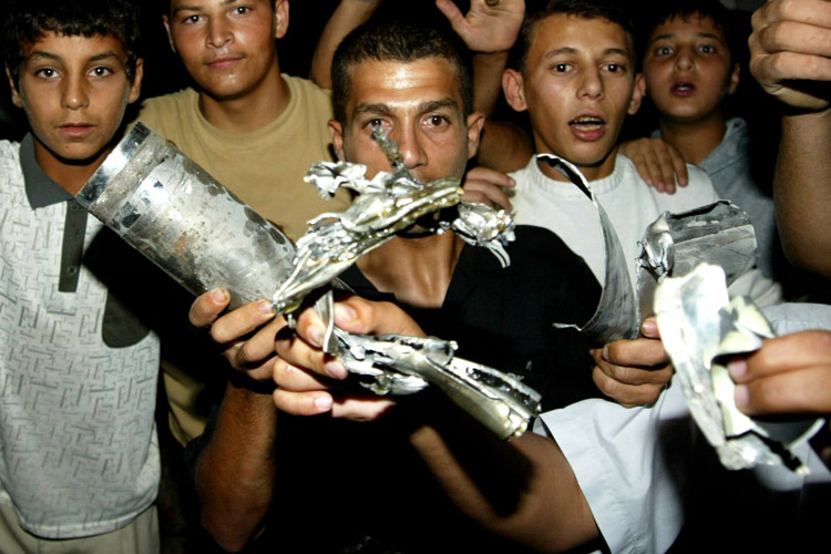 ISRAELI AIRCRAFT LAUNCH A SECOND SERIES OF AIRSTRIKES IN GAZA-Palestinian civilians display pieces from missiles in Khan Younis in Gaza Strip after Israeli helicopters fired missiles at Palestinian targets on July 16, 2005 in the Gaza Strip. Israeli aircraft launched a second series of airstrikes in Gaza City and the southern Gaza town of Khan Younis early Saturday. Two people were injured in the attacks. On Friday, Israeli air strikes killed five in the West Bank and Gaza, four of them Hamas militants.(UPI photo /Ismael Mohamad)