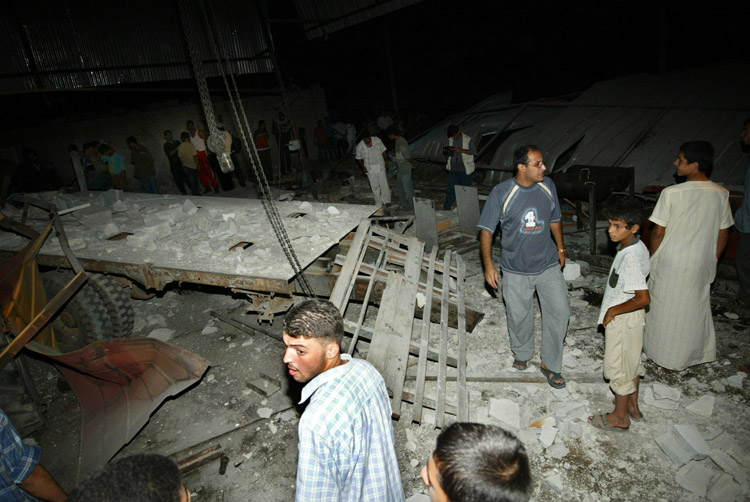 ISRAELI AIRCRAFT LAUNCH A SECOND SERIES OF AIRSTRIKES IN GAZA-Palestinian civilians gather at a destroyed workshop in Khan Younis in Gaza Strip after Israeli helicopters fired missiles at Palestinian targets on July 16, 2005 in the Gaza Strip. Israeli aircraft launched a second series of airstrikes in Gaza City and the southern Gaza town of Khan Younis early Saturday. Two people were injured in the attacks. On Friday, Israeli air strikes killed five in the West Bank and Gaza, four of them Hamas militants.    (UPI Photo /Ismael Mohamad)
