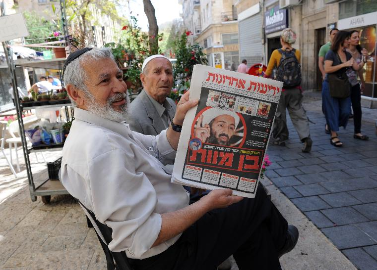 An Israeli holds a Hebrew newspaper in Jerusalem announcing the killing of Osama bin Laden by U.S. special forces in Pakistan: An Israeli holds  a Hebrew newspaper on Ben Yehuda Street in Jerusalem with headlines announcing the killing of Osama bin Laden