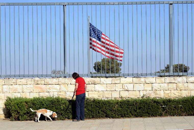 View Of American Consulate Building, Jerusalem: An Israeli walks a dog in front of an American flag flying behind a tall fence surrounding  the United States Consulate General building in Jerusalem, Israel, August 3, 2013. The US State Department has announced a plan to close dozens of US Embassies and Consulates in the Middle East and North Africa, including those in Yemen, Egypt, Iraq, Saudia Arabia and Israel on Sunday, after intercepting messages by senior Al-Qaeda members discussing attacks against American targets abroad. The United States has issued a warning to American citizens and travelers to avoid crowded areas.  UPI/Debbie Hill