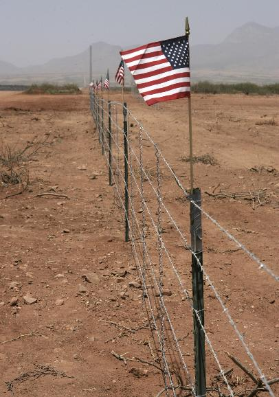 MINUTEMEN ACTIVE ON BORDER: Flags are displayed on the fence built by the Minutemen Project about 20 feet inside the US border with Mexico to help protect the ranch of John Ladd from illegal immigrants and Mexican cattle June 1, 2006 in Naco,  Arizona. Ladd says he recently spends more time repairing the border fence and returning cattle to Mexico than in any other activity.  He fears that diseased cattle will eventually cross the border and infect his animals.         (UPI Photo/Will Powers)