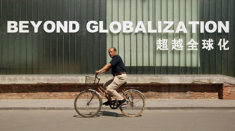 Man bicyces past studio in Beijing: A Chinese man bicycels past an energy power plant, next to an art studio claiming the world is