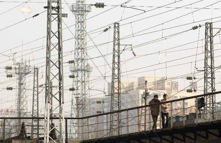 PEOPLE WALK ALONG A TRAIN TRACK: Two women traverse an overpass under a web of electrified train lines approaching one of Beijing's main train stations, in Beijing, China on February 9, 2006. The power-starved Chinese capital and nation grope for ways, including alternative energy sources, to fuel the growth, keeping the China engine running.  (UPI Photo/Stephen Shaver)