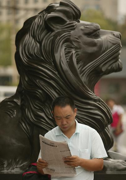 A Chinese man reads a newspaper next to a large guardian lion statue in Beijing: A Chinese man reads a newspaper next to a large guardian lion statue, common in Asia, outside a mall in Beijing on August 6, 2009.    China is executing a $586 billion stimulus package, announced last year which includes massive construction projects, to help the world's third-largest economy overcome the global economic slump. But Chinese experts warn that China's economic recovery was not yet on a solid footing, so an early end to the stimulus now coming from tax cuts and massive fiscal spending could lead to a new downturn.    UPI/Stephen Shaver
