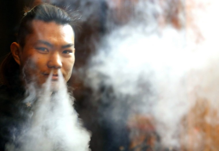 A Chinese man smokes in a restaurant in Beijing on February 27, 2015.  China, the world's largest consumer and producer of tobacco, was urged by the World Health Organization (WHO) to use graphic warnings on cigarette packages to help fight the tobacco epidemic.  Cigarettes kill about one million Chinese each year. Photo by Stephen Shaver/UPI