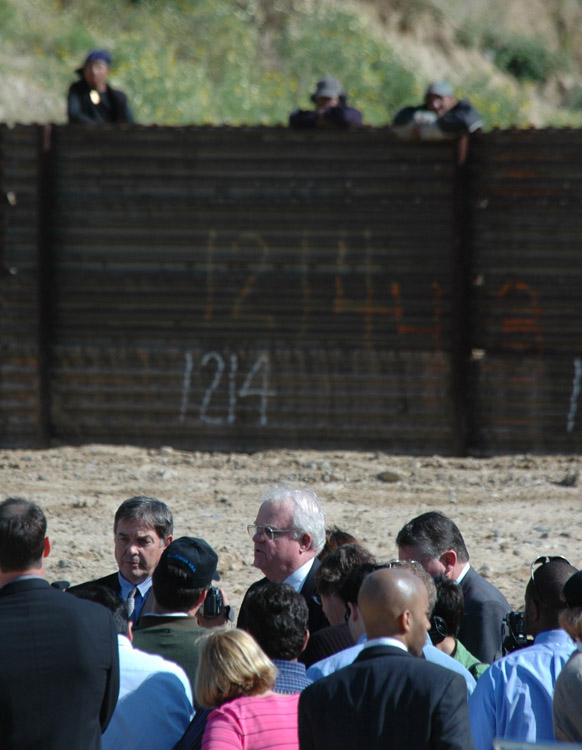 MEMBERS OF CONGRESS URGE COMPLETION OF BORDER FENCE-Three Mexican nationals look over the border fence from Mexico as, L-R, House Armed Services Committee Chairman Rep. Duncan Hunter,R-CA, House Chairman Rep. James Sensenbrenner,R-WI, and Rep. Randy Cunningham, R-CA, hold a press conference, March 29, 2005, along a single border fence in Smugglers Gulch near San Diego, California. They urged the completion of a fourteen mile fortified triple border fence along the San Diego border with Tijuana, Mexico in disregard to the environmental impact, The Endangered Species Act and other concerns related to the building of the fence. (UPI Photo/Earl S. Cryer)