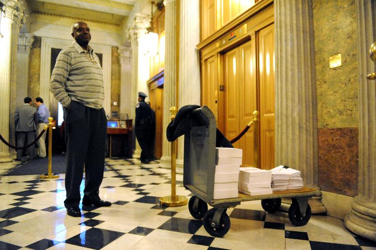 House and Senate meet to discuss the economic stimulus package in Washington: A worker with the House Appropriation Committee stands near a cart containing copies of the old and new economic stimulus package outside of a meeting with members of the House and Senate Appropriations Committee as they discuss the economic stimulus package on Capitol Hill in Washington on February 11, 2009. (UPI Photo/Kevin Dietsch)