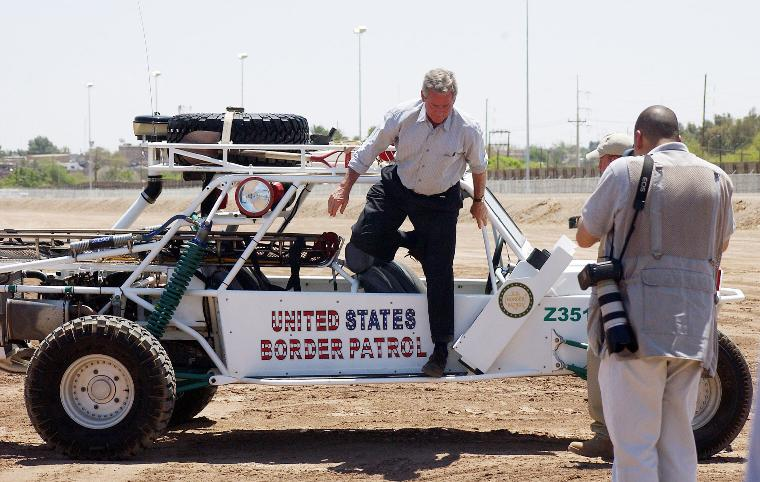 PRESIDENT BUSH VISITS THE BORDER TO PROMOTE IMMIGRATION REFORM: President bush climbs out of the Sand Rail that is used by the Border Patrol with driver Borstar Agent Rocky Kittle in San Luis, AZ on May 18, 2006. The President visited Yuma, Arizona Thursday and rode from there to the border town of San Luis, Arizona where he road in the sand rail. The wall behind the chainlink fence in the background is the Mexican border. (UPI Photo/Terry Ketron/Pool/Yuma Sun)