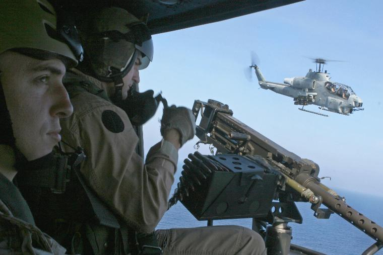 Marines patrol Gulf of Aden skies for pirates: An AH-1 helicopter escorts a UH-1Y helicopter while U.S. Marine Corps Staff Sgt. Bryan E. Campbell prepares an M2.50 caliber machine gun in support of counter-piracy surveillance operations over the Gulf of Aden, April 6, 2009. Hijacked Maersk-Alabama cargo ship captain Richard Phillips was rescued by U.S. Navy forces, killing three pirates, on April 12, 2009.  (UPI Photo/Robert C. Medina/U.S. Marines)